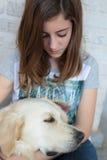 Él es muchacha durmiente con su perro en sus brazos Foto de archivo