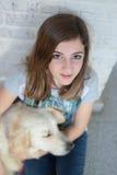 Él es muchacha durmiente con su perro en sus brazos Imagen de archivo libre de regalías