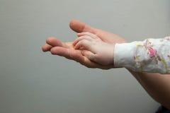 Él mano del ` s del niño descansa en la palma de un adulto Fotos de archivo