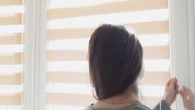 Él muchacha feliz despertó y cogió las cortinas en la ventana, y los rayos del sol cayeron en ella Un joven sonriente almacen de metraje de vídeo
