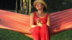 Él muchacha mira en el smartphone Mujer sonriente mujer joven relajada que mira el teléfono móvil en hamaca metrajes