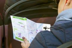 Él muchacha se sienta en el bus turístico, auriculares que llevan, escucha la historia de la guía y considera el mapa de Málaga imagenes de archivo