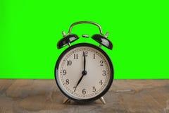 Él reloj del ` del ` s siete o ya, hora de despertar para el desayuno, despertador metálico negro viejo del vintage Fotografía de archivo