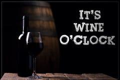 Él reloj del vino o del ` s Un vino rojo del opf de la botella y un vidrio con la barra Foto de archivo