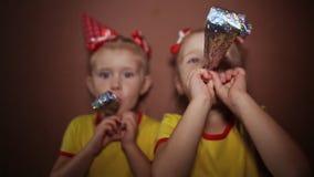 Él ` s al día de fiesta Dos pequeñas hermanas gemelas encantadoras en vestidos rojos y casquillos cónicos en sus cabezas están so metrajes