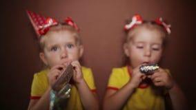 Él ` s al día de fiesta Dos pequeñas hermanas gemelas encantadoras en vestidos rojos y casquillos cónicos en sus cabezas están so almacen de video