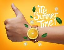 Él tipografía del tiempo de verano del ` s Pulgar encima de la naranja de la fruta de la mano que lleva Foto de archivo libre de regalías