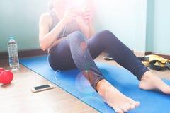 Élaboration femelle de forme physique sur le tapis de yoga avec la bouteille d'eau et l'équipement de sport, la séance d'entraîne Photographie stock libre de droits