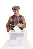Électeur mûr mettant un vote dans une boîte de vote Image stock