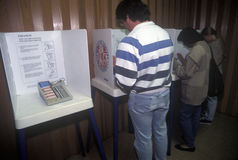 Électeurs et cabines de vote dans un bureau de vote Photos stock