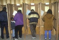 Électeurs et cabines de vote dans un bureau de vote, CA Photos stock