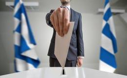 Élection ou référendum en Grèce L'électeur tient le vote ci-dessus disponible d'enveloppe Drapeaux grecs à l'arrière-plan photographie stock