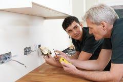 Électricien With Apprentice Working dans la nouvelle maison Photo libre de droits
