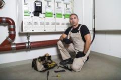 Électricien avec la boîte d'outils asseyant près de la distribution ou du panneau de fusible images stock