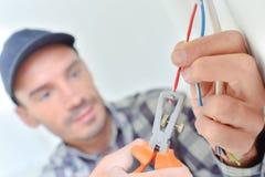 Électricien coupant un fil d'un coup de ciseaux image libre de droits