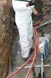 Électricien dans l'excavation de route pendant le travail de réparation d'un grand images stock