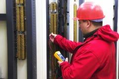 Électricien dans le circuit de commande rouge avec le multimètre Images stock