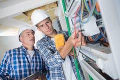 Électricien de stagiaire travaillant au fusebox sous la surveillance photographie stock libre de droits