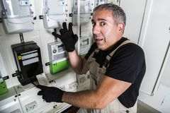 Électricien drôle faisant la réparation dans le standard ou le mètre de l'électricité images libres de droits