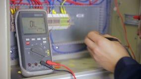 Électricien examinant le courant électrique Tension industrielle d'essai d'électricien d'usine utilisant le multimètre à l'élém.  banque de vidéos