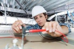 Électricien féminin installant le dispositif électrique dans le plafond photographie stock libre de droits