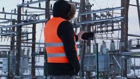 Électricien filmé avec la tablette aux centrales en hiver banque de vidéos