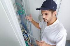 Électricien focalisé appliquant la procédure de sécurité tout en travaillant au panneau électrique images stock