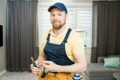 Électricien positif réparant des fils dans l'appartement image libre de droits