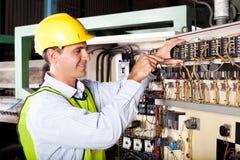 Électricien réparant la machine industrielle image stock