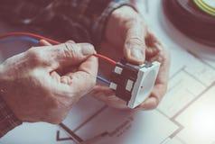 Électricien reliant un fil dans une prise de puissance Photographie stock libre de droits