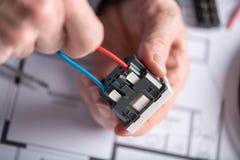 Électricien reliant un fil dans une prise de puissance Image libre de droits