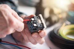 Électricien reliant un fil dans une prise de puissance, effet de la lumière Images libres de droits