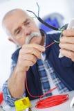 Électricien supérieur occasionnel au travail Photo stock