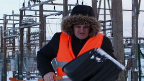 Électricien vérifiant la pelle à neige aux centrales en hiver clips vidéos