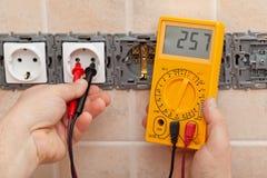 Électricien vérifiant la tension dans un élém. élect. partiellement installé Photos libres de droits