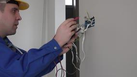 Électricien vérifiant la tension de prise utilisant le multimètre dans une prise de montage de mur clips vidéos