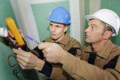 Électriciens câblant la nouvelle maison image stock