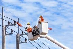 Électriciens réparant le fil de la ligne électrique Images stock