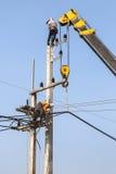 Électriciens réparant le fil de la ligne électrique avec la grue Image libre de droits
