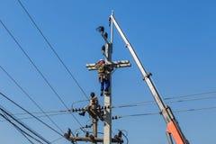 Électriciens réparant le fil de la ligne électrique sur le poteau de courant électrique avec la grue Photographie stock libre de droits