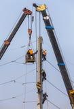 Électriciens réparant le fil sur le poteau de puissance de l'électricité avec la plate-forme hydraulique Photos stock