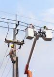 Électriciens réparant le fil sur le poteau de puissance de l'électricité avec la plate-forme hydraulique Image libre de droits