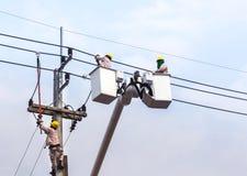 Électriciens réparant le fil sur le poteau de puissance de l'électricité avec la plate-forme hydraulique Photo stock