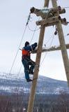 Électriciens travaillant à un poteau en hiver Photo stock