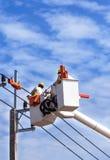 Électriciens travaillant dans la taille sur la plate-forme hydraulique de panier Photo stock