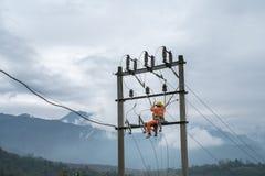 Électriciens travaillant haut sur le poteau de l'électricité au Vietnam Images libres de droits