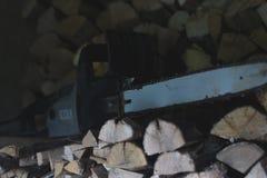 Électrique a vu sur une pile de bois de chauffage avec le fond brouillé Image libre de droits