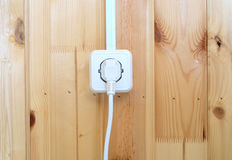 Électriques blancs branchent la prise sur le mur en bois avec les planches verticales Photos libres de droits