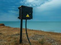 Électro mètre dans la perspective du lever de soleil en mer Photographie stock