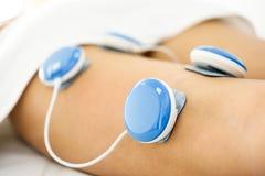 Électro stimulation dans la physiothérapie à une jambe de jeune femme Photographie stock libre de droits